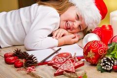 Girl in Santa hat writes letter to Santa near christmas de Royalty Free Stock Photo