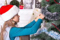 Girl in santa hats decorating the Christmas tree Stock Image