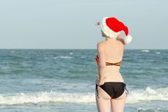 Girl in Santa hats with the inscription New Year on the back loo Royalty Free Stock Images