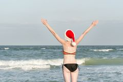 Girl in Santa hats with the inscription New Year on the back. Sea shore. Hands raised up. Back view Stock Photo
