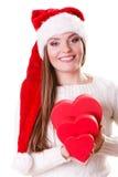 Girl santa helper hat holds heart shaped gift boxes Stock Image