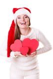 Girl santa helper hat holds heart shaped gift boxes Stock Photography