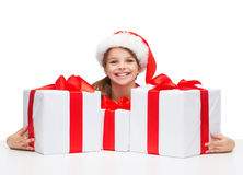Girl in santa helper hat with many gift boxes Stock Photos