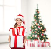 Girl in santa helper hat with many gift boxes Stock Images