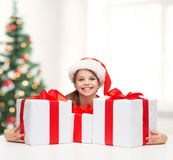 Girl in santa helper hat with many gift boxes Stock Photo