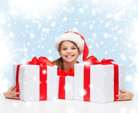 Girl in santa helper hat with many gift boxes Royalty Free Stock Images