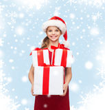 Girl in santa helper hat with many gift boxes Stock Photography