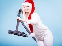 Girl in santa helper hat with vacuum cleaner Stock Photo