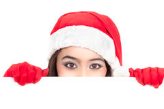 Girl in Santa peeking over sign board. Girl in Santa peeking over paper sign board. Cute funny photo closeup of christmas woman with copyspace. Isolated on white Royalty Free Stock Photography