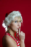 Girl in Santa's cap. Santa girl asking for silence Stock Photo