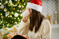 Girl in Santa`s cap drinks coffee near the Christmas tree. Stock Photography