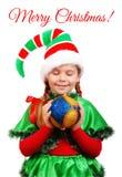 Girl Santa`s elf with Christmas ball over white Stock Photos