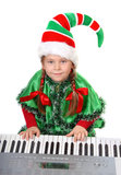 Girl - Santa's elf plays a synthesizer. Stock Images