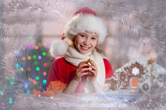 Girl in Santa's hat with decoration ball in hands Royalty Free Stock Image