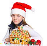 Girl in Santa's hat with gingerbread house Stock Photography