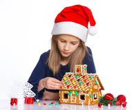 Girl in Santa's hat with gingerbread house Stock Photos