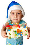 Girl in Santa's hat giving out s present Royalty Free Stock Photo