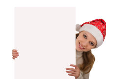 Girl in Santa's hat holding empty board. Pretty Girl in Santa's hat holding empty board royalty free stock image