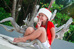 Girl on Santa's hat making silence gesture. Girl on Santa's hat sitting outdoor among tropical trees smiling and making silence gesture Stock Photo