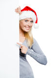 Girl in Santa's hat pointing at copyspace Stock Photo
