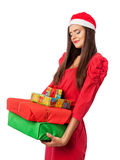 Girl in a Santa's helper hat holding christmas gifts. Girl in red dress holding christmas gifts Royalty Free Stock Images