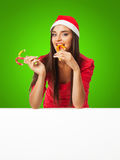 Girl in a Santa's helper hat standing near a big white and  holds Stock Photos