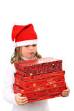 Girl in Santa's red hat carrying three presents Royalty Free Stock Images