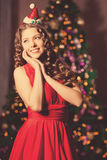Girl in a santa suit. Against the background of lights Christmas Royalty Free Stock Image