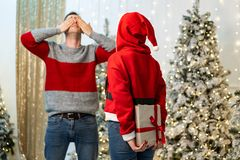 Girl in santa sweater get ready to give a gift and the guy is waiting for covering his eyes with his hands stock image