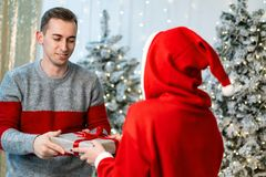 Girl in santa sweater giving a gift to the handsome guy royalty free stock photos