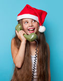Girl in Santas hat calling by phone Stock Photo