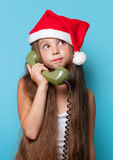 Girl in Santas hat calling by phone Stock Photography