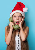 Girl in Santas hat calling by phone Royalty Free Stock Photography