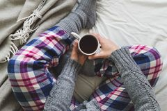 Girl sat on bed in cozy pyjamas drinking a cup of tea. Woman sat on a bed in cozy pyjamas and socks, drinking mug of tea Royalty Free Stock Photography