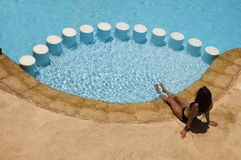 Girl sat by a swimming pool. A tanned girl relaxing with her toes in the water of a small pool Stock Image