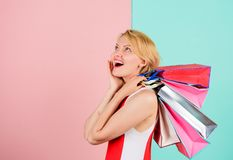Girl satisfied with shopping. Girl enjoy shopping or just got birthday gifts. Woman red dress hold bunch shopping bags. Blue pink background. Tips to shop sales royalty free stock photography