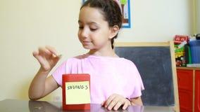 Girl saving money in money box stock video