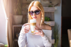 Girl savouring delicious coffee Royalty Free Stock Image