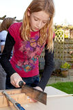 Girl is sawing a wooden stick Royalty Free Stock Photos