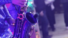 A girl with a saxophone, a musical group of girls with a saxophone perform on stage, a blue dress, a stage light, a stock video footage