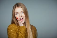 Girl saying secret news gossip looking aside. Mysterious girl in sweater with palm sheltering lips looking ae saying secret news gossip smiling on grey studio stock images