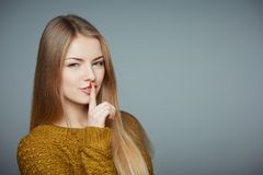 Girl saying secret news gossip looking aside. Secrecy concept. Mysterious girl in sweater with finger on lips looking at camera on grey studio background royalty free stock images