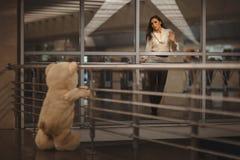 Girl says goodbye with a teddy bear. Sad girl waving, she says goodbye with a teddy bear and it's very sad Royalty Free Stock Images