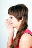 Girl says something in secret. Blue-eyed girl says something in secret behind his hand royalty free stock image