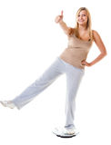 Girl on scales celebrating weightloss Royalty Free Stock Image