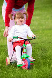 Girl scared of riding a bicycle Stock Images