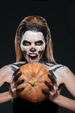 Girl with scared skeleton makeup holding pumpkin and shouting stock photography