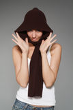 Girl with a scarf. The young woman with a brown scarf on a grey background royalty free stock images