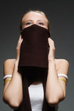 Girl with a scarf. The young woman with a brown scarf on a grey background royalty free stock photo