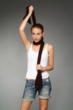 Girl with a scarf. The young woman with a brown scarf on a grey background royalty free stock photography
